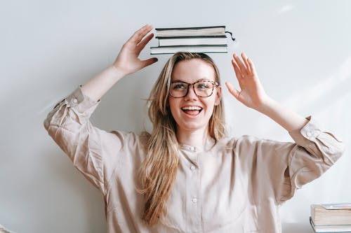 Happy student with heap of books on head