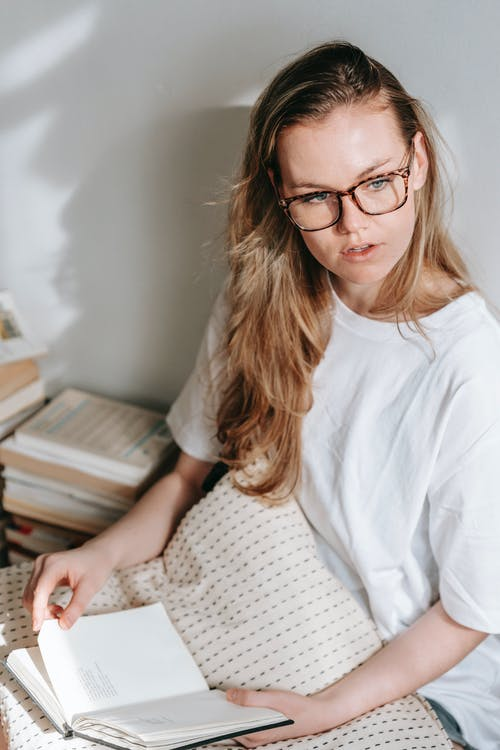Young pensive woman in eyewear sitting with cushion and journal against textbooks while looking away in house