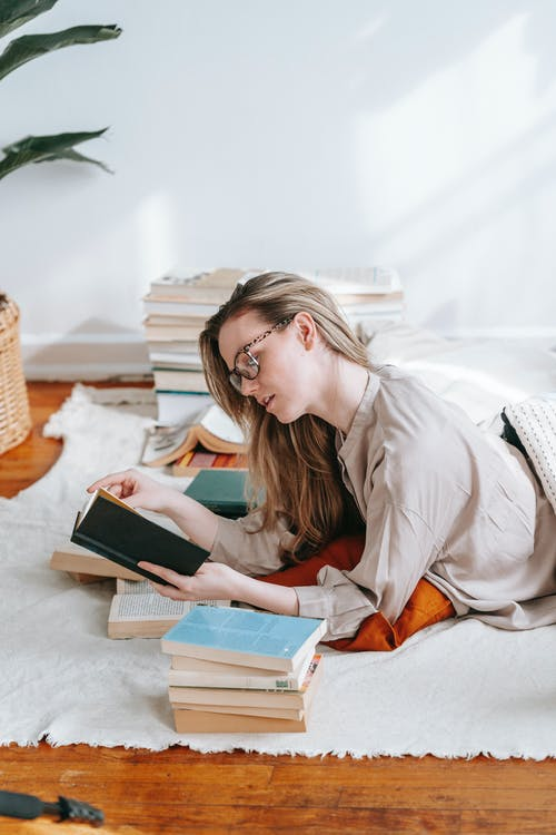Focused student reading textbook while studying on carpet in house