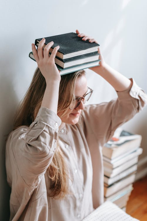 High angle of female in eyeglasses sitting near wall and putting books on head for improving balance