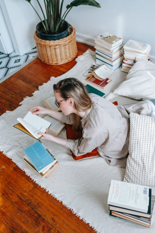 Young woman reading different books for research