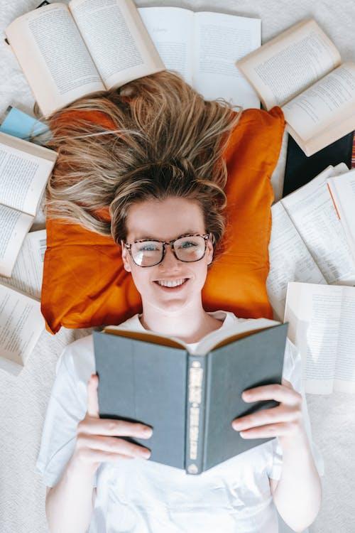 Smiling woman reading novel while lying among opened books