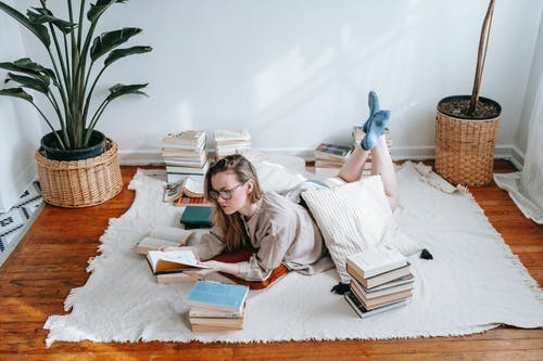 Full body of female in eyeglasses reading book while lying on plaid near heap of literature and green plants