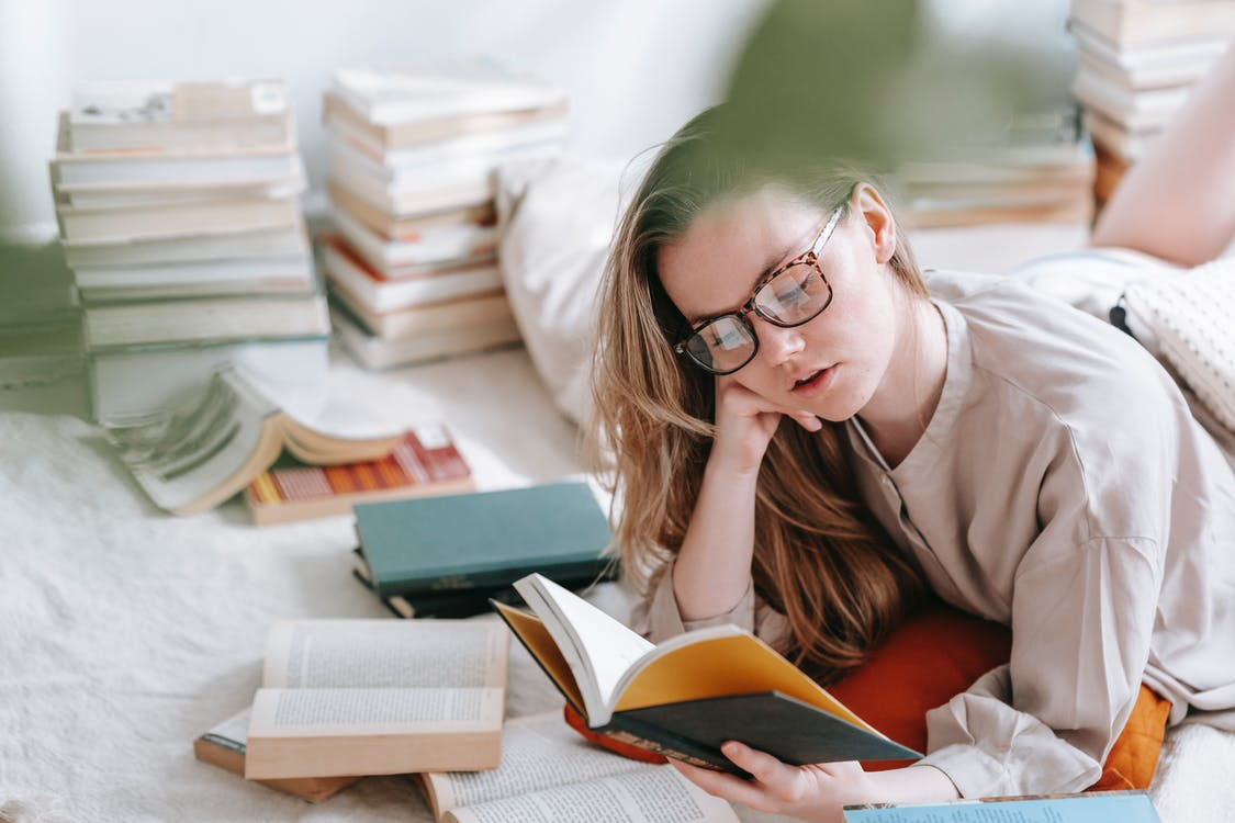 Concentrated young female in eyeglasses reading book while lying on white blanket near heap of literature in light room at home