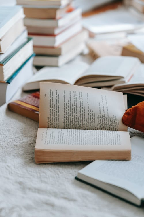Collection of closed and opened books with text placed on white fabric in light room at home with various literature