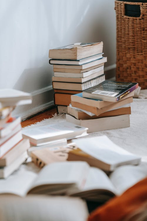Collection of books placed on white soft textile on floor near wall in light room with wicker basket at home