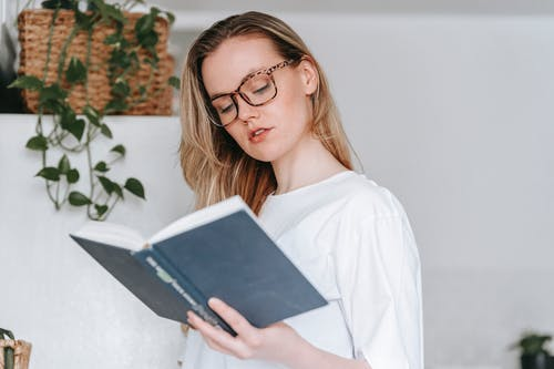 Concentrated young female in eyeglasses and white garment reading book while standing in light kitchen with fridge and green plant