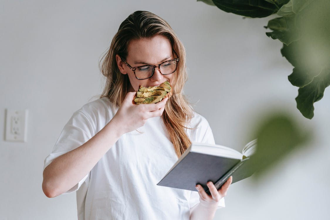 Young woman with book and toast