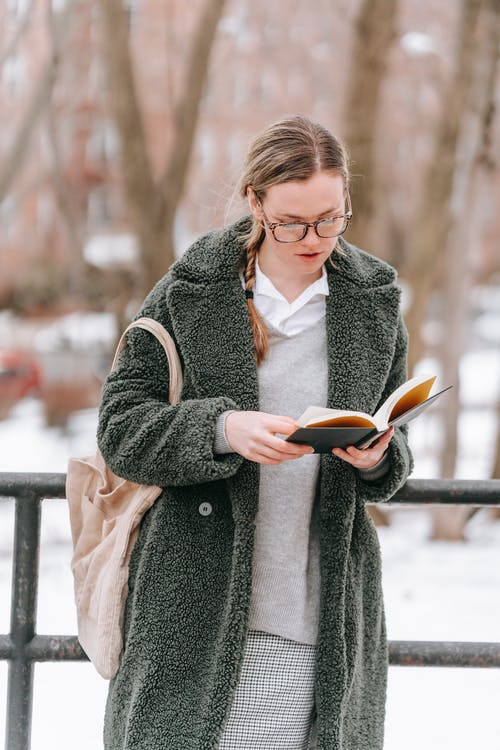 Young woman with paper book in winter park