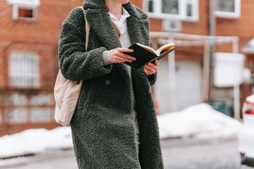 Crop unrecognizable woman in coat with textile bag reading textbook while studying on city street