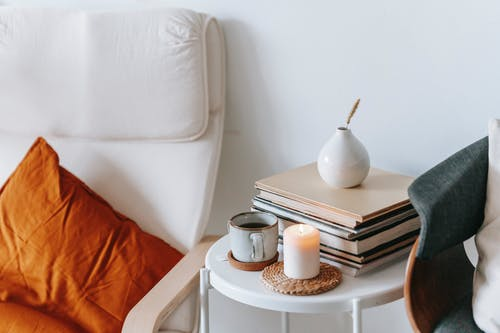 Table with tea and burning candle between armchairs in house