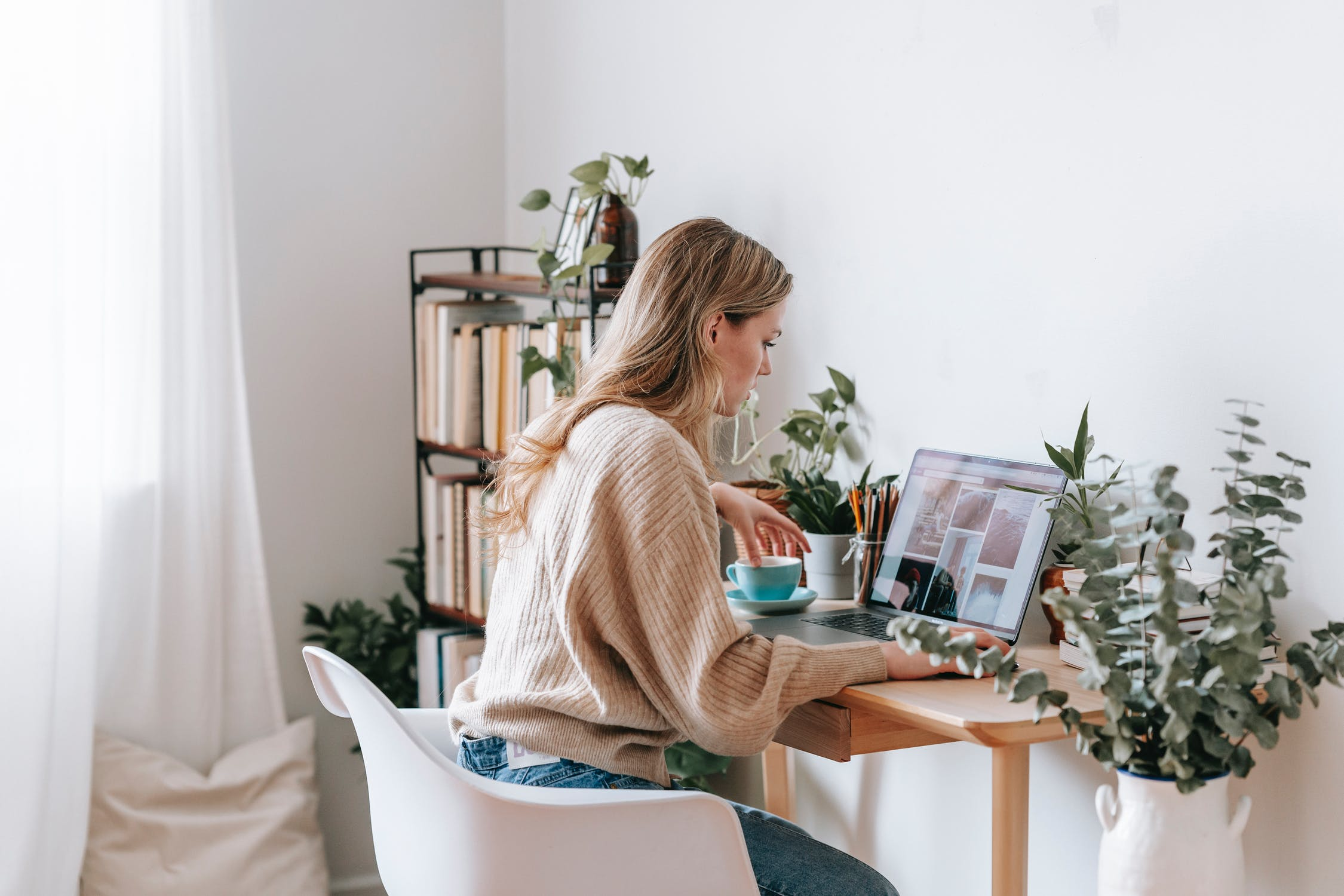 Woman in tan jumping working from home as a freelancer