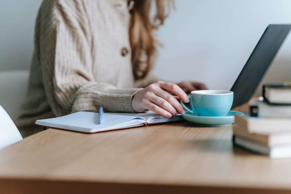 Crop anonymous female freelancing with netbook at table with mug of coffee on blurred background