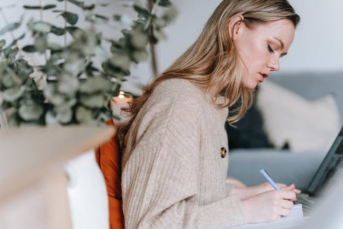 Woman writing in notebook near laptop