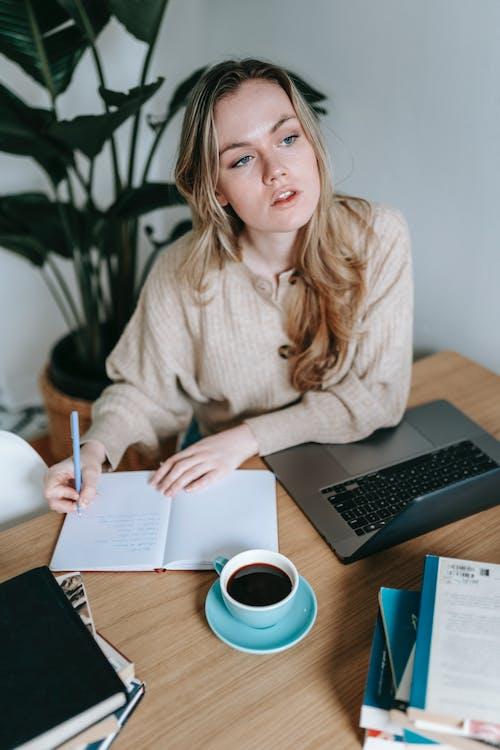 Focused businesswoman writing in notebook near laptop