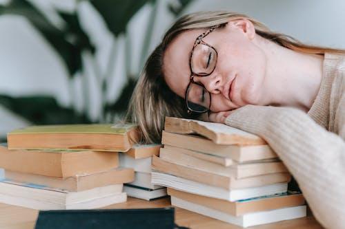 本のスタックで眠っている疲れた女性