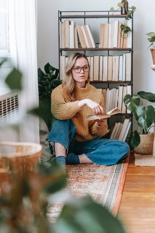 Pensive young female in casual outfit holding book and sitting on floor in light living room with bookshelf and plants while looking away