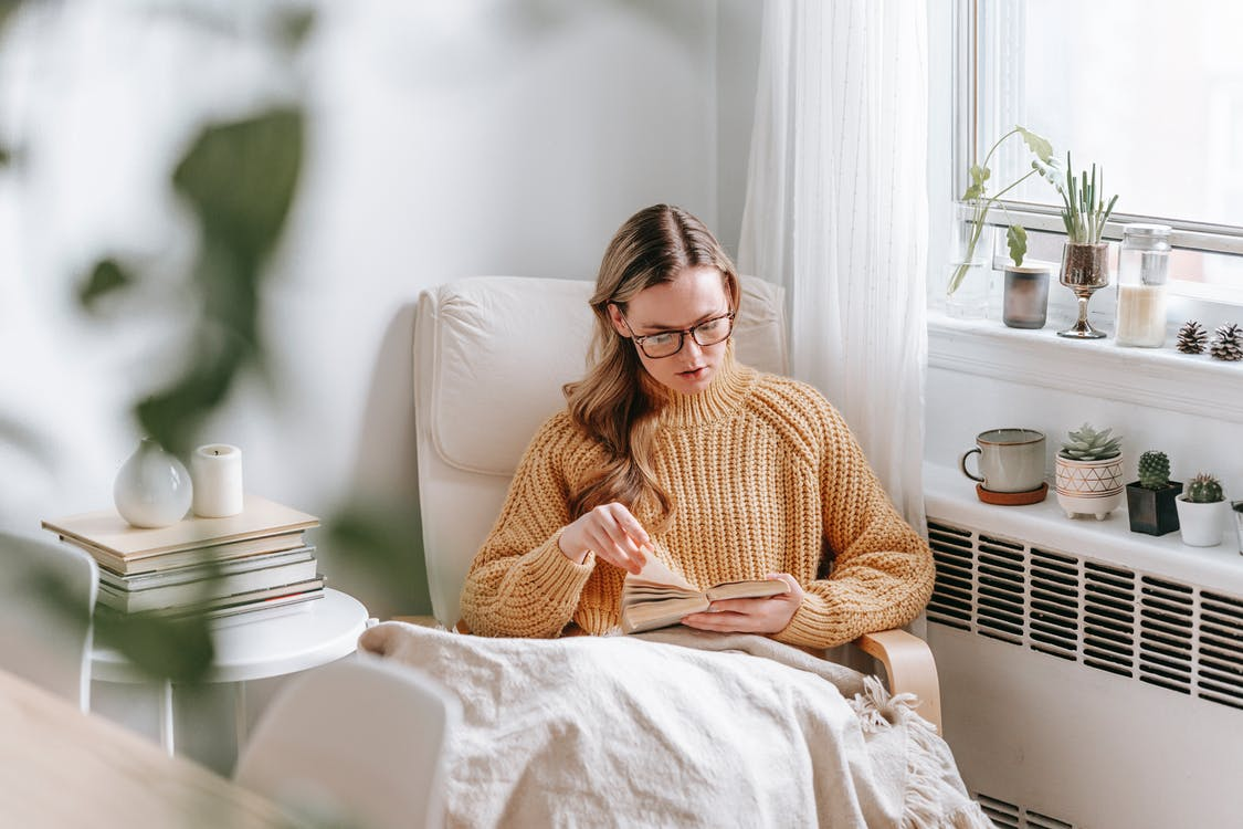 Young female in casual clothes sitting in armchair with plaid and reading interesting book while resting in cozy room at home