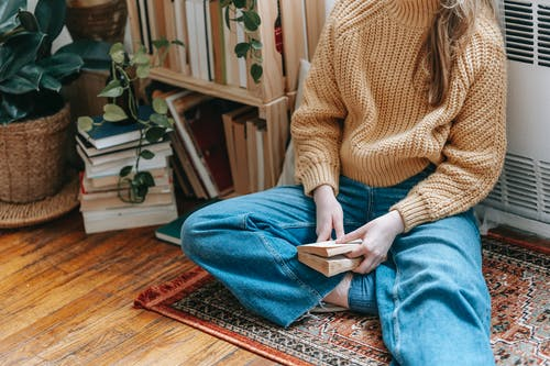 Crop unrecognizable female in stylish warm sweater and jeans sitting on floor at home while reading interesting novel during weekend