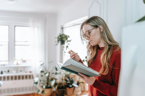 Smart lady reading textbook during breakfast at home