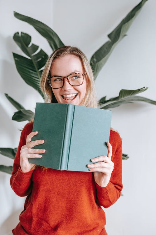 Joyful young female student with blond hair in sweater and eyeglasses smiling and looking away while standing near white wall with book in hands after success in exam