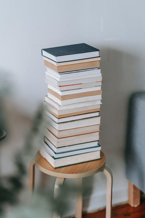 Stack of Books Placed on Wooden Stool