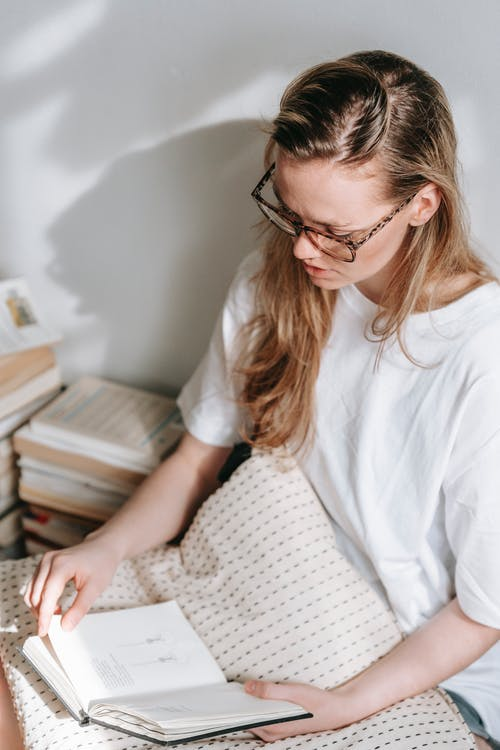 From above of serious young lady with long hair in white t shirt and eyeglasses sitting on floor with pillow near stack of books and reading interesting novel in daylight