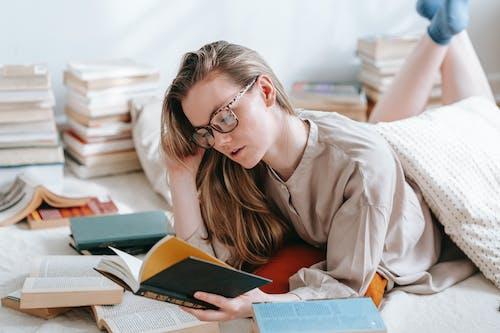 Focused woman reading book on floor