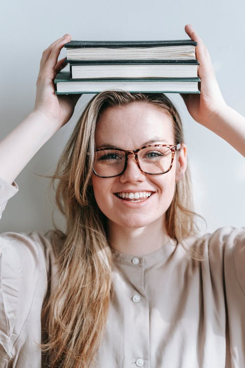 Cheerful woman with books on head