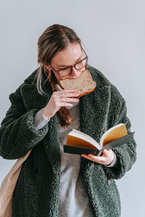 Concentrated female wearing warm coat and eyeglasses eating tasty bread while reading interesting book on white background in light room