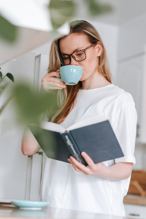 Woman drinking coffee while reading book in kitchen