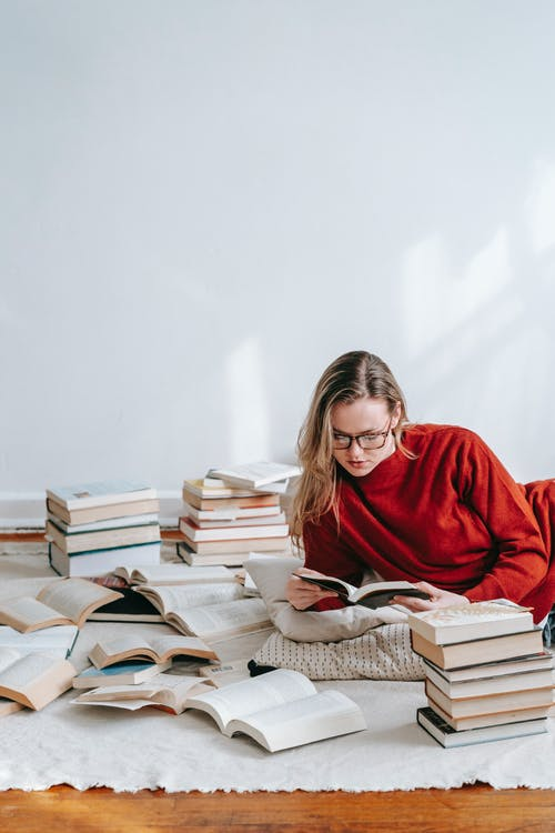 Concentrated woman reading book on floor