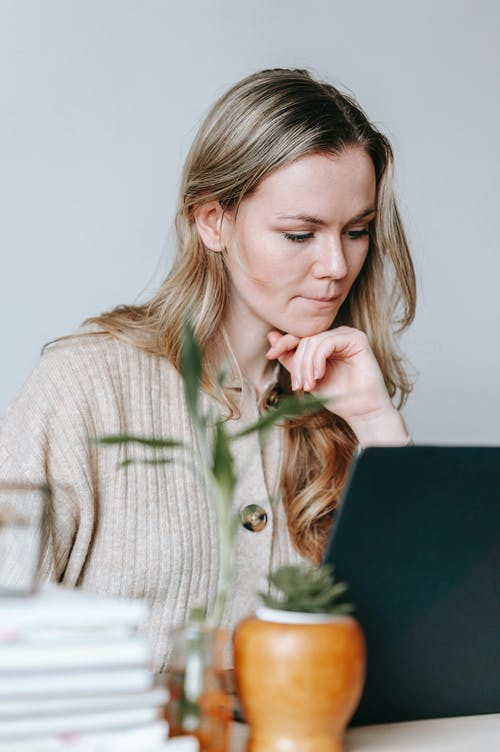 Pensive woman browsing laptop in room
