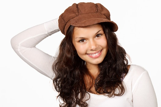 Woman in White Scoop Sleeved Shirt and Brown Cap Smiling