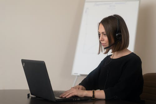 Female operator working on laptop with headphones with microphone