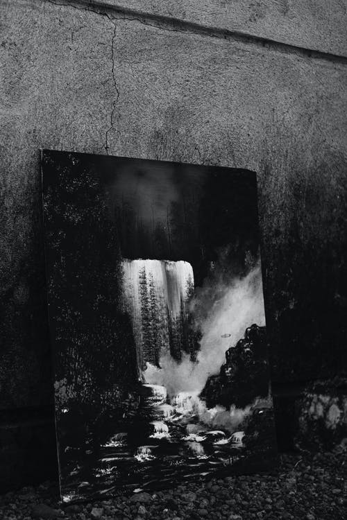 Black and white creative picture of waterfall falling down from cliff in woods placed near wall with crack on street