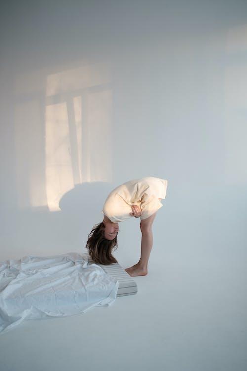 Young woman bending forward near mattress