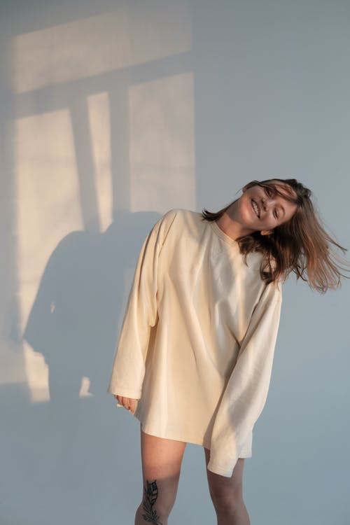 Happy young female in white sweatshirt smiling and shaking hair while dancing against gray wall