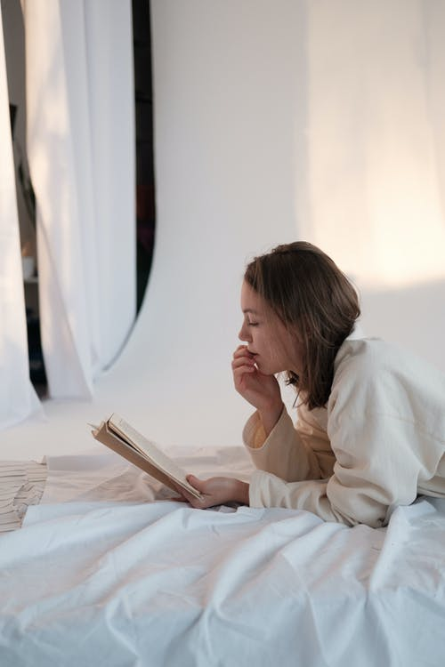 Side view of young woman touching face and reading interesting story while relaxing on mattress in morning