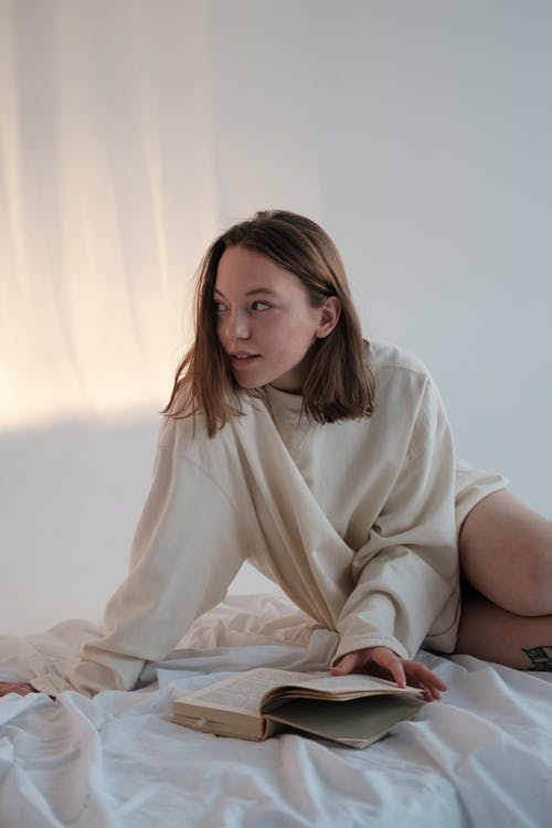 Young female in sweatshirt smiling and looking away while reading book on mattress against white wall