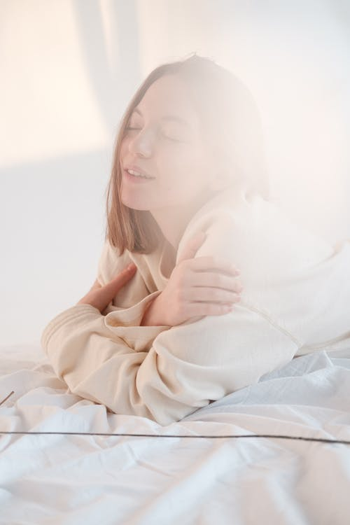 Young female with closed eyes touching shoulders and enjoying softness of sweatshirt while resting on bed in morning