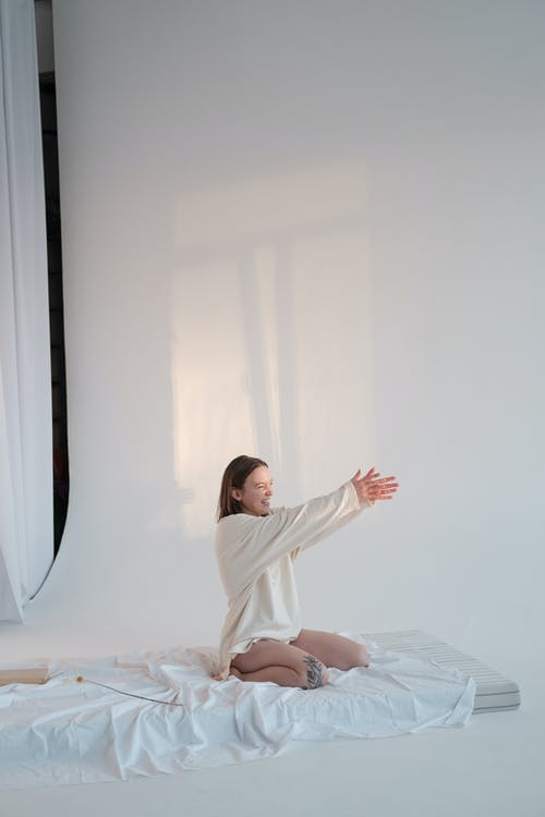 Delighted young female in sleepwear smiling and stretching out arms to touch sunlight while sitting on soft mattress against white background in morning