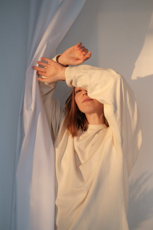 Young female in sweatshirt covering face with raised arms and looking at camera while standing near white curtain in sunlight