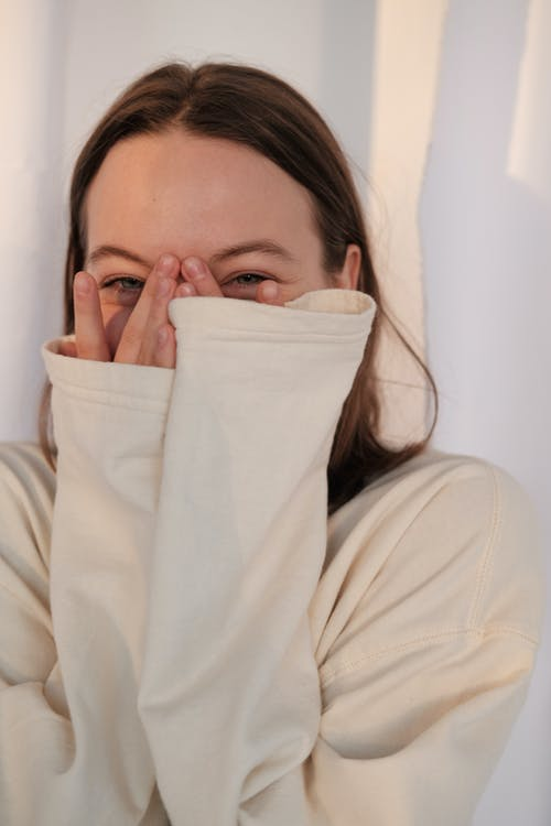 Young woman laughing and covering face
