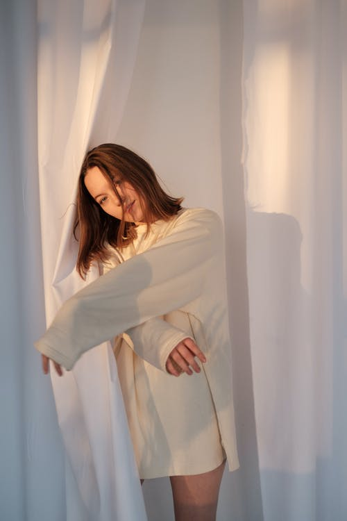 Young woman in sweatshirt leaning on white curtain and looking at camera in light room