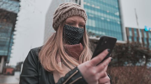 Woman in Black Jacket Holding Black Iphone 7