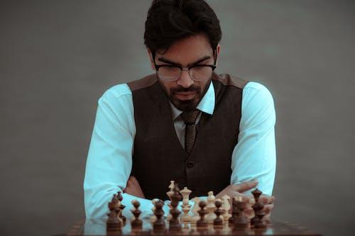 Crop thoughtful man playing chess in studio