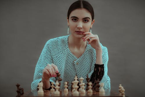 Focused ethnic female player making chess move while playing game at table against gray background