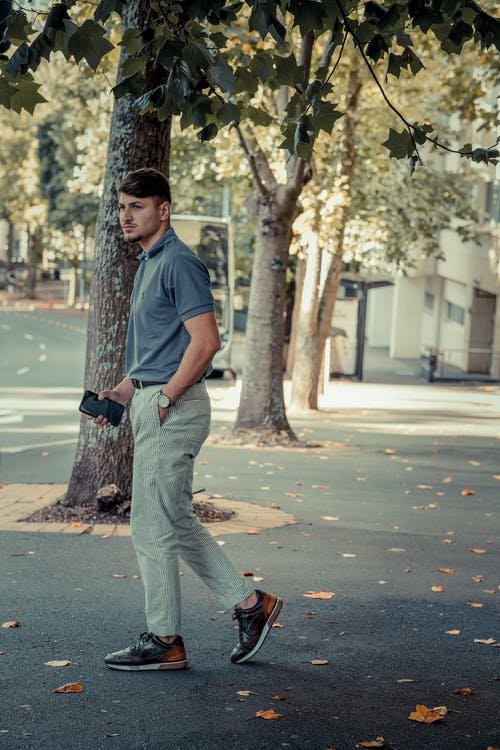 Man in Blue Polo Shirt and Gray Denim Jeans Standing on Sidewalk