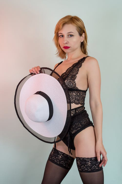 Young provocative woman in black underwear and nylon stockings with lace holding stylish hat while looking at camera